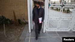 Conservative Iranian parliamentarian Ali Motahari leaves Interior Ministry building in Tehran after registering as a legislative candidate for Iran's 2012 election.