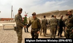 A U.S. soldier and an Afghan soldier shake hands during a handover ceremony in Helmand on May 2.