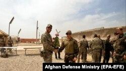 Një ushtar amerikan dhe një ushtar afgan shtrëngojnë duart gjatë një ceremonie të dorëzimit të detyrave në provincën Helmand, më 2 maj.