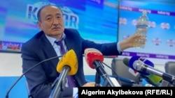 Глава Минздрава Алымкадыр Бейшеналиев на пресс-конференции демонстрирует бутылку с отваром иссык-кульского корня. Бишкек. 16 апреля 2021 года.