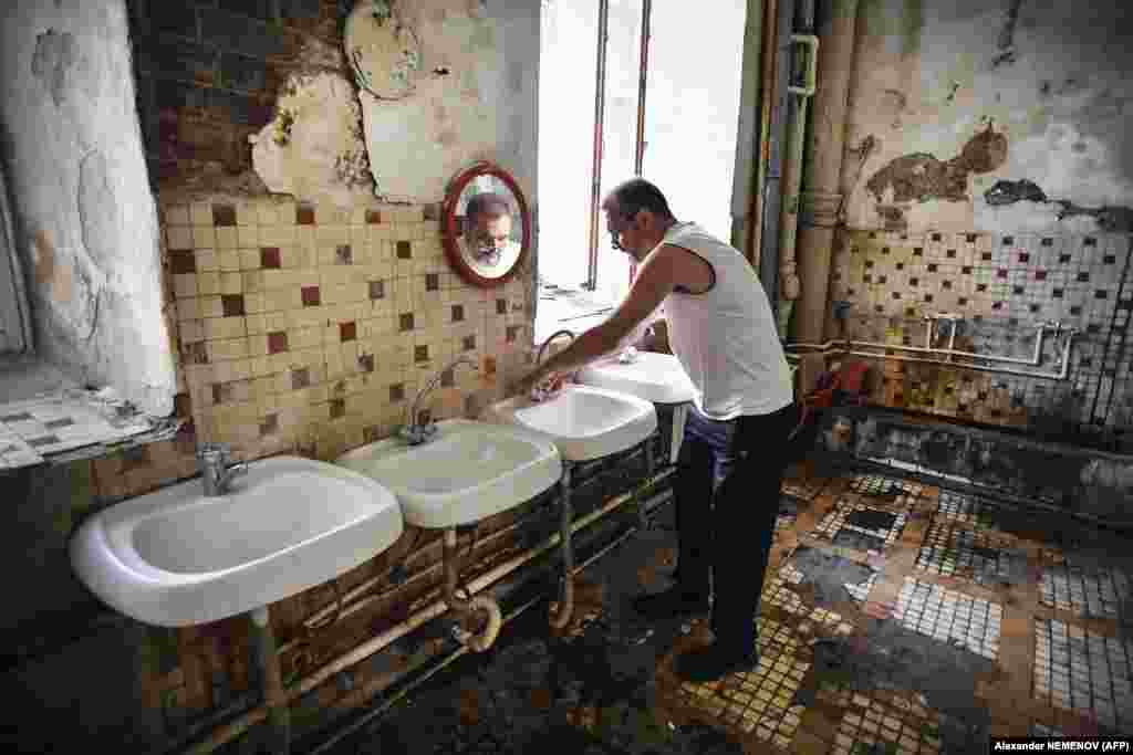 "Vladimir Mogilnikov, 62, cleans his hands in a communal washroom. ""Hundreds of people live here, often five to a room, with moldy walls and rusty, leaking pipes,"" he says."