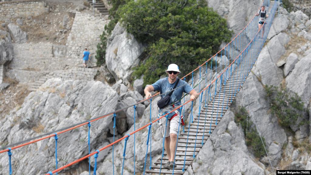 Однак піднятися на вершину скелі можна безплатно крутими кам'яними сходами (на задньому плані)