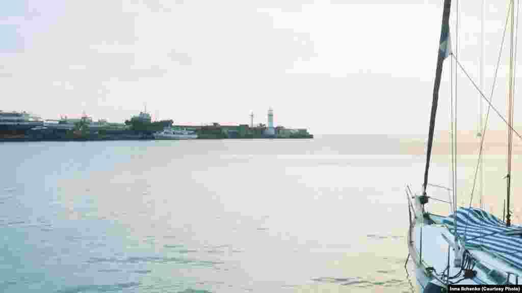 Пришвартована яхта з краєвидом на Ялтинський маяк