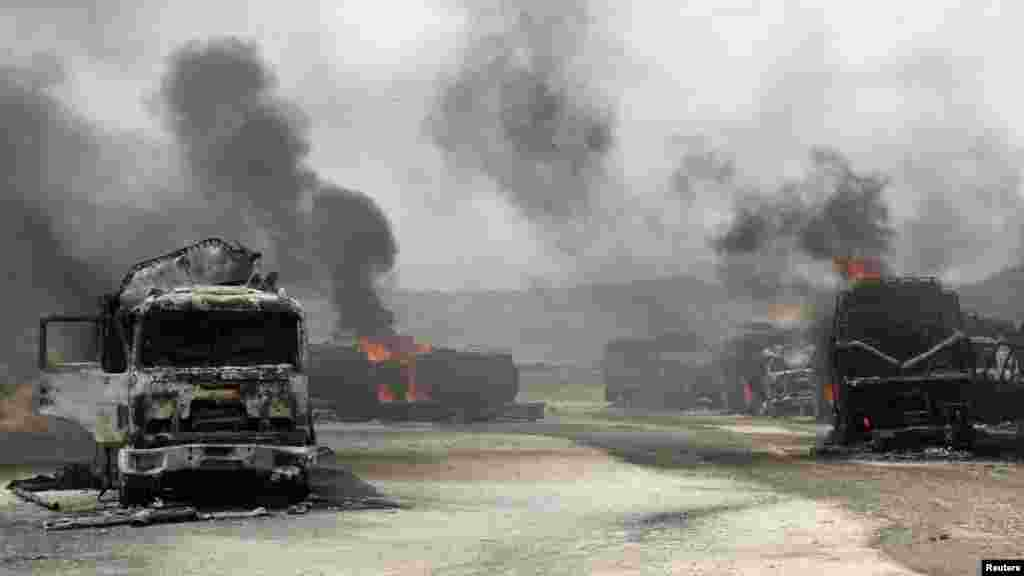 Smoke rises from burning NATO supply trucks in Samangan Province on July 18. A bomb planted by the Taliban destroyed 22 NATO trucks carrying supplies to their forces in northern Afghanistan. (REUTERS)