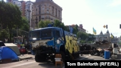 A water cannon truck that was captured and destroyed by activists still stands on the square.