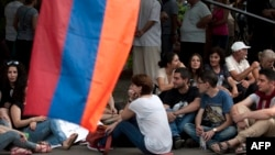 Armenia -- Demonstrators sit on a street during a protest against an increase of electricity prices in Yerevan, June 26, 2015