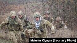 Павло Чиркін (крайній зліва) допомагає виносити пораненого з поля бою