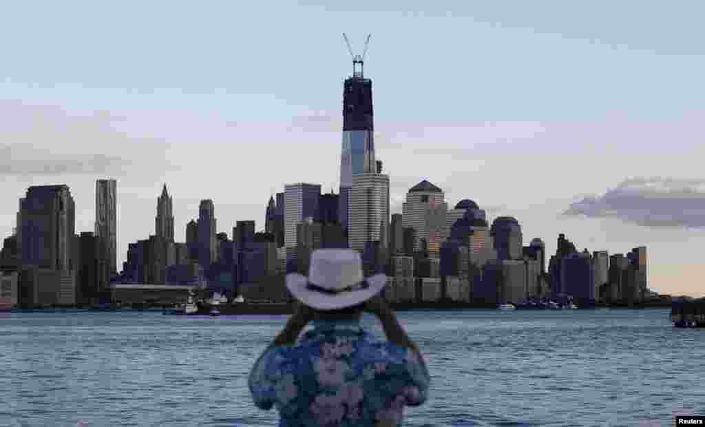 One World Trade Center stands tall on the skyline as a man takes a picture from in Hoboken, New Jersey, on September 9, 2012.
