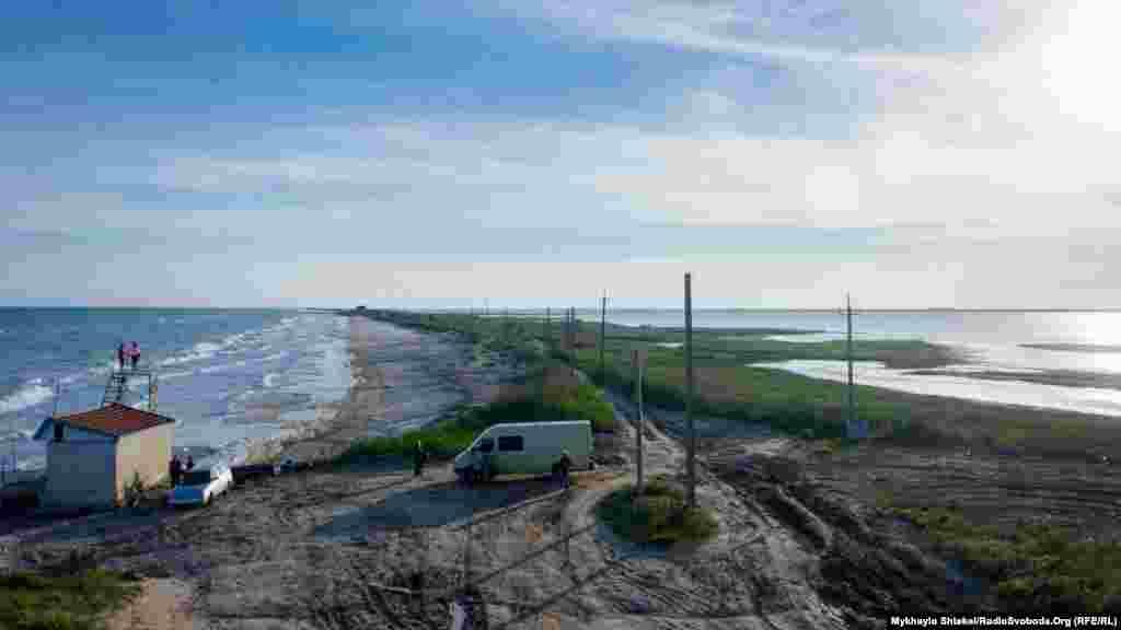 Піщана коса, що розділяє море (зліва) і лиман (справа). Влітку на цьому пляжі багато туристів, тут працюють атракціони для дітей. Поки що на морському березі тихо, працівники облаштовують вежу для гірки.