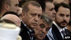 اردوغان (در کنار عبدالله گل، رئیسجمهوری پیشین ترکیه) در مراسم تدفین یکی از دوستانش که در جریان کودتا کشته شد