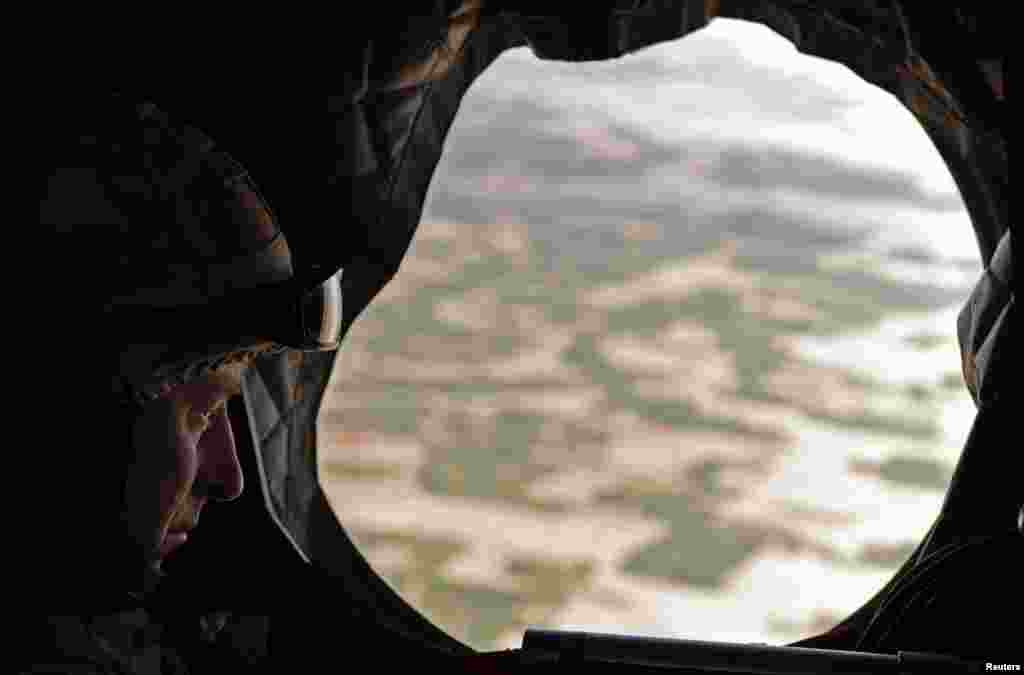 Britain's Prince Charles looks through the window of a British military helicopter en route to Lashkar Gah in March 2010.