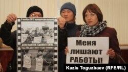 """Журналисты закрытой по решению суда газеты """"Голос республики"""" стоят с плакатами в руках в здании суда. Алматы, 22 февраля 2013 года."""
