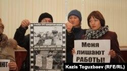 """Журналисты закрытой по решению суда оппозиционной газеты """"Голос республики"""" держат плакаты в фойе здания суда. Алматы, 22 февраля 2013 года."""