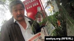 Ғалымбек Толғанбаев темір жол вокзалының алдында газет сатып тұр. Алматы, 11 тамыз 2011 жыл.