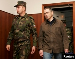 Khodorkovsky is escorted by a security officer before an appeal hearing against his fraud conviction in Moscow City Court on September 20, 2005.