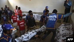 Pakistani volunteers bring the bodies of suspected militants to a hospital in Karachi on February 23.