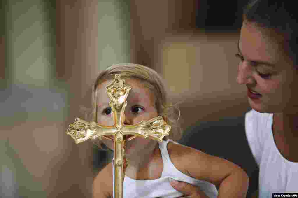 KOSOVO -- Anarita Mihilli, is being held by her mother as she kisses the gold plated cross in the church of the Black Madonna, during the feast of Assumption in the village of Letnica, Kosovo, Saturday, Aug. 15, 2018.
