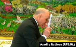 Түркіменстан президенті Гурбангулы Бердімұхаммедовтың кітабын сүйіп тұрған адам.