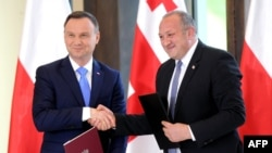 Georgian President Giorgi Margvelashvili (right) and Polish counterpart Andrzej Duda exchange documents during a joint press conference following their meeting in Tbilisi on May 30.