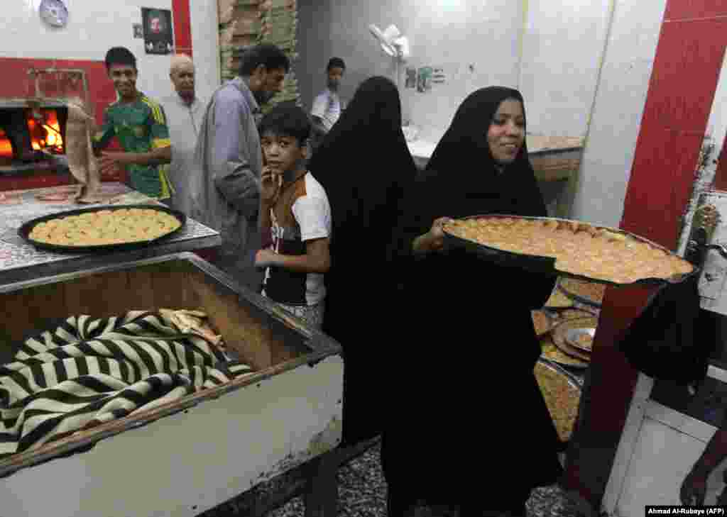 A woman carries a tray of sweets that are prepared at a bakery for the occasion of Eid al-Fitr holiday in Baghdad's Sadr City neighborhood in Iraq.