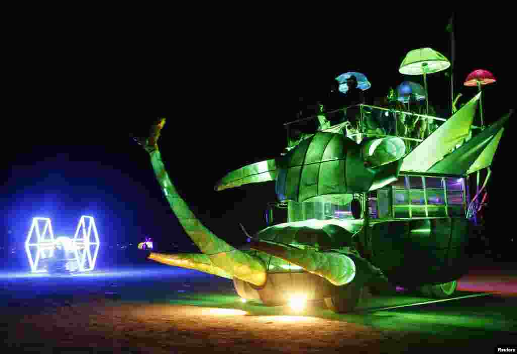 Mutant vehicles drive across the main area during the Burning Man 2013 arts and music festival in the Black Rock Desert of Nevada.