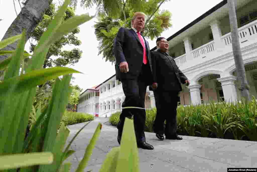 Дональд Трамп и Ким Чен Ын прогуливаются в саду после двусторонних переговоров.