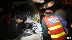 Rescue workers and police move the bodies of the victims of a suicide bomb attack in Lahore on November 2, 2014.
