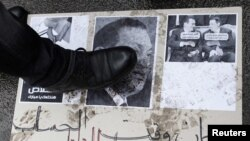 Demonstrant gazi plakat sa Mubarakovom fotografijom, 4. februar 2011