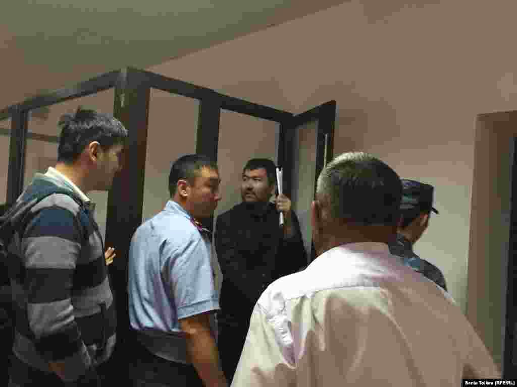 Талгат Аян выходит из отсека, где сидят арестанты в зале суда.