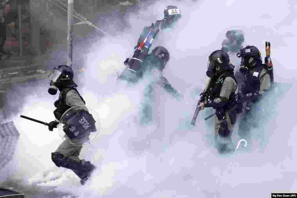 Police in riot gear move through a cloud of smoke at the Hong Kong Polytechnic University in Hong Kong, November 18, 2019.