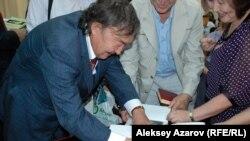 Олжас Сулейменов ставит дарственную надпись на своих книгах. Алматы, 2 июня 2015 года.