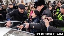 Полицейские сажают в автомобиль Ингу Иманбай. Алматы, 22 февраля 2020 года.