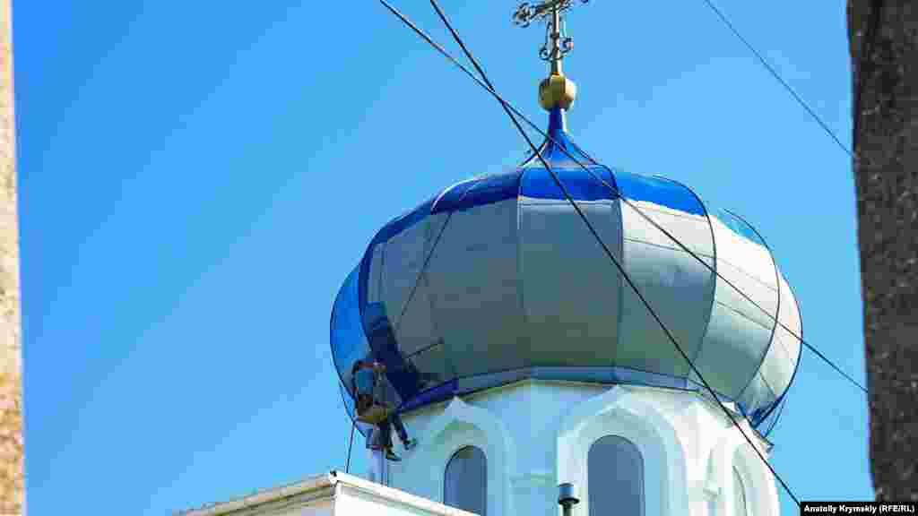 Boyacılar Muqaddes Kseniya Peterburgskayanıñ baş kilsesiniñ qubbesini boyalay