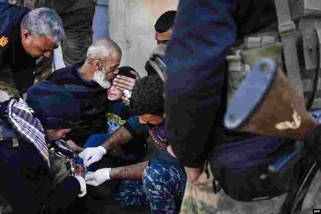 An elderly Iraqi man comforts a wounded boy as he receives treatment from military doctors in Mosul during a military operation by Iraqi security forces against Islamic State militants. (AFP/Dimitar Dilkoff)
