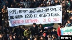 """متظاهرون ضد الرئيس السوري بشار الأسد في مدينة إدلب يرفعون لافتة تقول: """"عيد ميلاد سعيد قداسة البابا من سوريا حيث قتل الأسد بابا نوئيل""""."""