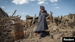 An earthquake victim stands near damaged houses in the earthquake-stricken Iranian town of Azerbaijan on August 13.