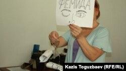 """Активистка движения """"За справедливость"""" держит в руках весы, которые символизируют: коррупция перевесила законность на весах казахстанской Фемиды. Алматы, 27 августа 2014 года."""