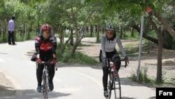 Iran -- Women on bicycle in a park Iran, Apr2011