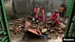 Villagers sit on the debris of their house after it was damaged during the recent exchange of fire between Pakistan and India at the Pakistani border town of Dhamala Hakimwala near Sialkot on October 8, 2014.