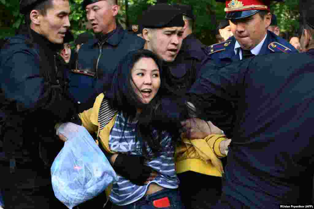 Kazakh police officers detain opposition protesters in Almaty on May 1. (AFP/Ruslan Pryanikov)