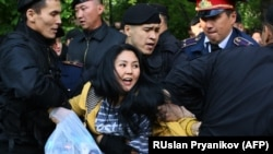 Kazakh police officers detain opposition protesters in Almaty on May 1.