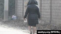 Жительница Кайнарбулака идет по утопающей в грязи улице. Шымкент, 3 ноября 2014 года.