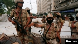 Paramilitary soldiers stand guard near the dismantled makeshift tents of the supporters of Muttahida Qaumi Movement (MQM) political party after a protest, in Karachi on August 22.