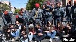 Полицейские пытаются разблокировать проезжую часть улицы в столице Армении на месте акции протеста с участием студентов. Ереван, 16 апреля 2018 года.