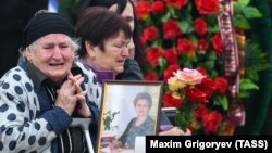 Relatives of the Kerch school-attack victims grieve at a ceremony to pay their last respects in the city center on October 19.