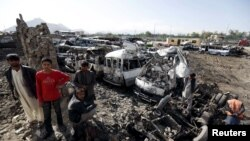 Residents stand at the site of yesterday's suicide car bomb attack on a government security building in Kabul on April 20.