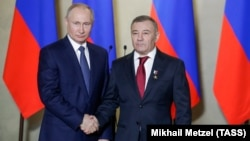 Russian President Vladimir Putin (left) awards a Hero of Labor gold star to his childhood friend, oligarch Arkady Rotenberg, in 2018.