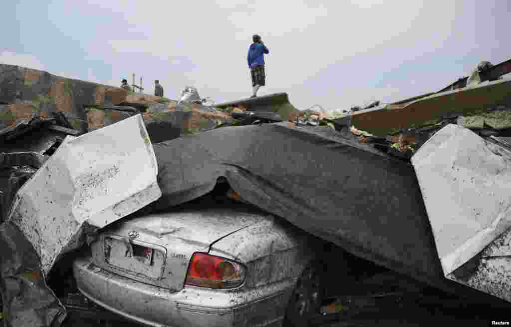 A resident stands on top of wreckage after the tornado struck the town, destroying dozens of homes, two schools, and a hospital.