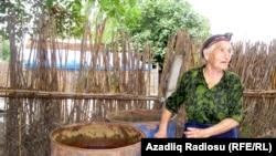 Азербайджанка стоит возле бочек с водой.