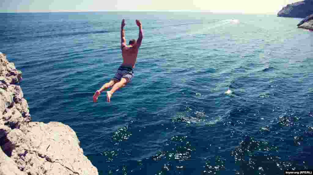 Ныряльщик прыгает с горы у грота Шаляпина в Новом Свете вблизи Судака
